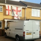 Photo of house with flags and van